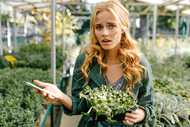 Linda chica joven, con cabello rojo claro y ojos verdes, vestida con un vestido verde oscuro, posando mientras sostiene su teléfono inteligente en sus manos