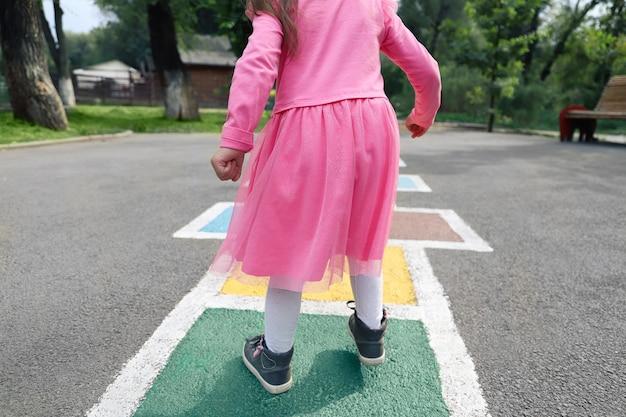 Linda chica joven jugando a la rayuela en el patio trasero