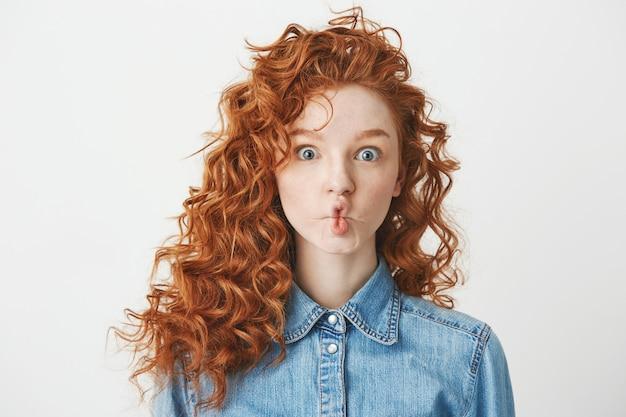 Linda chica joven con el pelo rizado astuto haciendo cara divertida. copia espacio