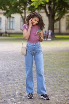 Linda chica joven de piel oscura en el parque