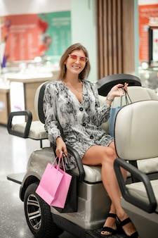Linda chica joven posando mientras está sentado con bolsas de compras, que sostiene en sus manos en un automóvil para un centro comercial. expresando alegría y felicidad. comprar fue un éxito. viernes negro descuentos
