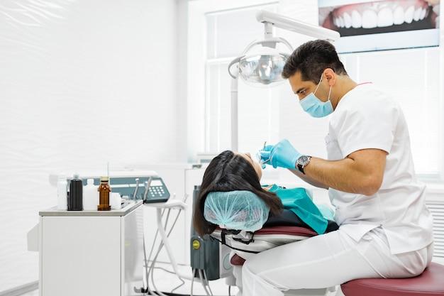 Linda chica joven está siendo examinada por el dentista