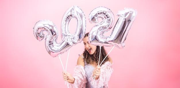 Linda chica joven con una sonrisa en un traje festivo posando sobre un fondo de estudio rosa y sosteniendo globos plateados para el concepto de año nuevo