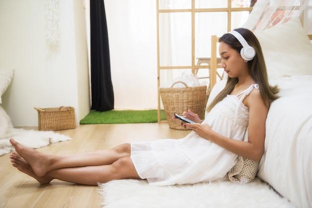 Linda chica juega smartphone en dormitorio