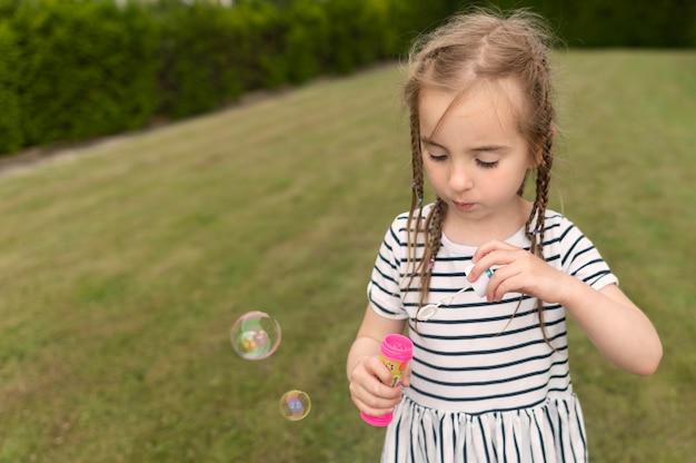 Linda chica jugando con soplador de burbujas