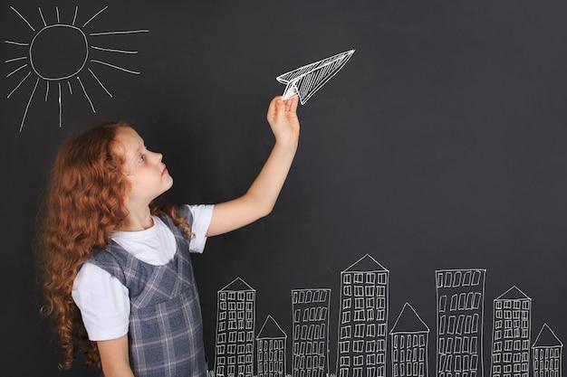 Linda chica lanzando avión de papel dibujando en la pizarra
