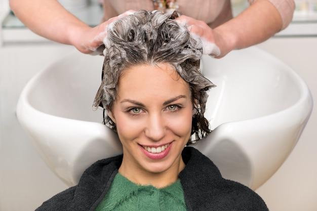 Linda chica lavando su cabello en el salón