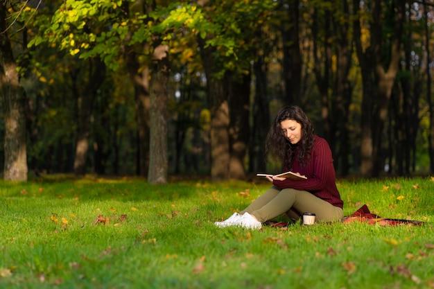 Una linda chica lee un libro y bebe café.