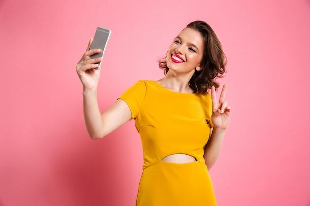 Linda chica linda con maquillaje brillante que muestra gesto de paz mientras toma selfie en teléfono móvil