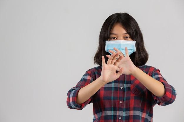 Linda chica lleva máscara y haciendo parada de mano de otro prople en la pared blanca.