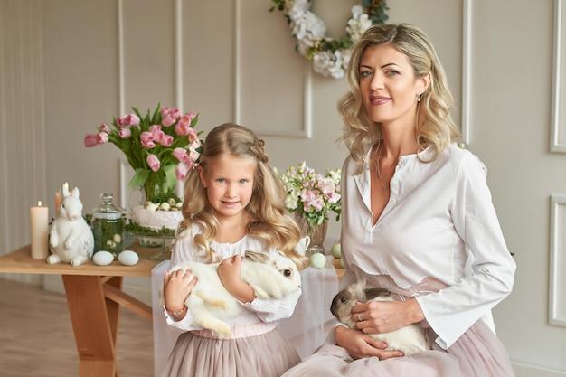 Linda chica y madre jugando con conejos