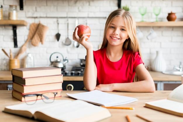 Linda chica con manzana estudiando en casa
