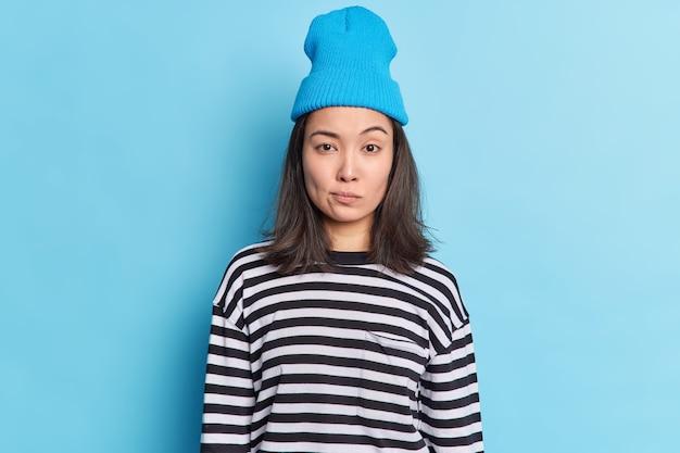 Linda chica milenaria con cabello oscuro ha determinado una expresión seria, levanta las cejas, hace suposiciones, mira directamente, usa un sombrero, un jersey informal a rayas