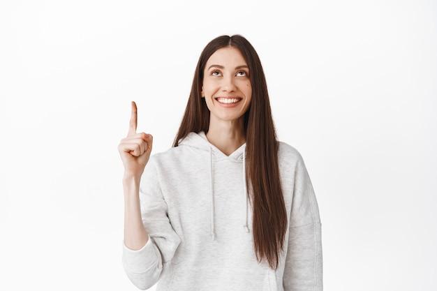 Linda chica milenaria mirando algo arriba, señalando con el dedo en la parte superior y sonriendo complacida, encontró un anuncio promocional genial, mostrando un enlace o logotipo, de pie contra una pared blanca
