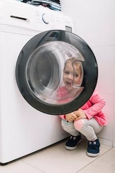 Linda chica mirando a través de la puerta de la lavadora