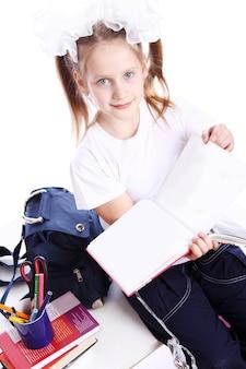 Linda chica con mochila sentado en el escritorio