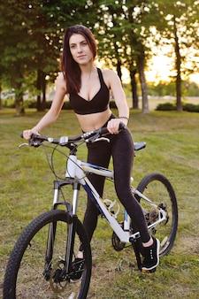 Linda chica montando una bicicleta en el parque en una naturaleza