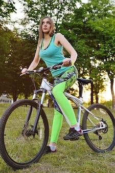 Linda chica montando una bicicleta en el parque en una superficie de la naturaleza