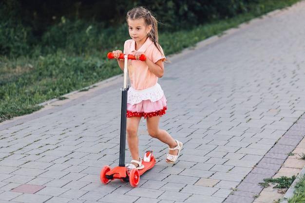 Linda chica montando scooter de empuje rojo en pasarela