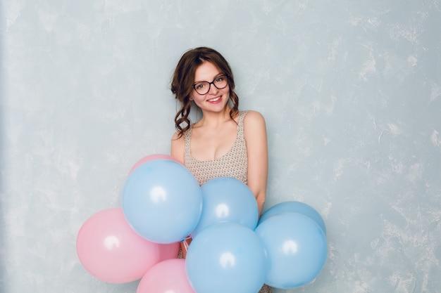 Linda chica morena de pie en un estudio, sonriendo ampliamente y sosteniendo globos azules y rosas.
