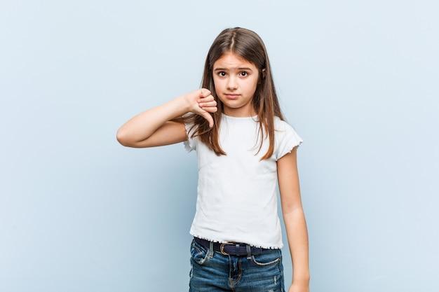 Linda chica mostrando un gesto de disgusto, pulgares hacia abajo. concepto de desacuerdo
