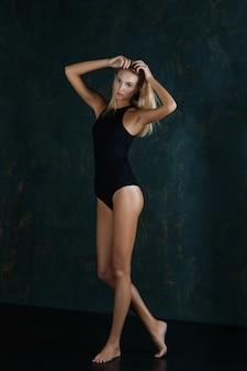 Linda chica nadadora en traje de baño negro cerrado