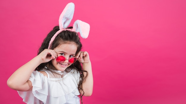 Linda chica en orejas de conejo ajustando gafas de sol