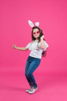 Linda chica en orejas de conejo bailando