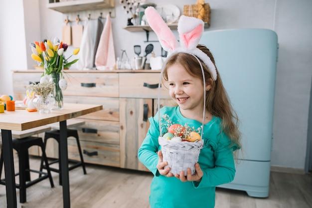 Linda chica en orejas de conejo con canasta con huevos de pascua