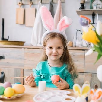 Linda chica en orejas de conejo pintando huevos para pascua