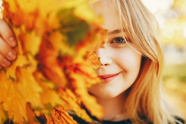 Linda chica en un parque de otoño