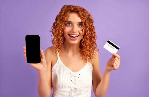 Linda chica pelirroja con rizos sostiene una tarjeta de crédito y muestra una pantalla de teléfono inteligente negra aislada en una pared violeta. pago en línea, banca.