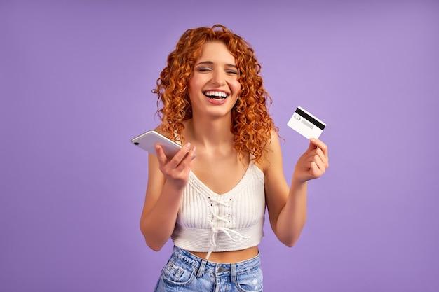 Linda chica pelirroja con rizos tiene una tarjeta de crédito y un teléfono aislado en una pared violeta. pago en línea, banca.