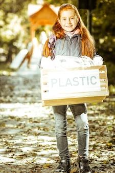 Una linda chica pelirroja sosteniendo una caja llena de plástico en un buen día