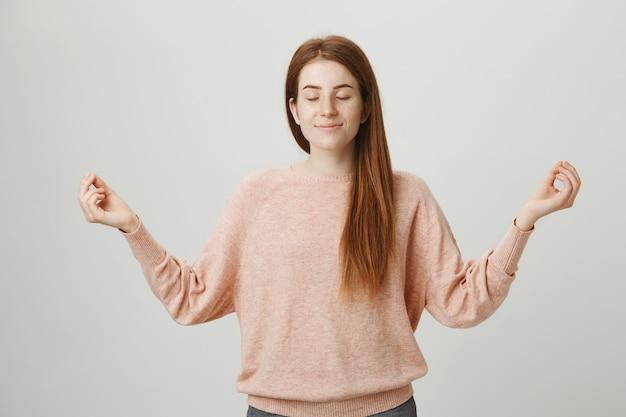 Linda chica pelirroja tranquila meditando, levanta las manos en gesto zen