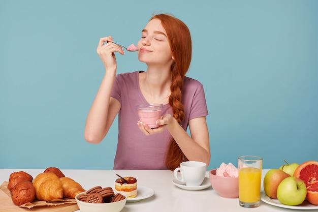 Linda chica pelirroja tratando de degustar yogur de cereza, cerró los ojos de placer, lame una cucharadita sentada en la mesa durante el almuerzo
