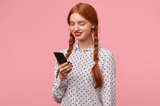 Linda chica pelirroja con trenzas sosteniendo un teléfono en la mano lee un mensaje y sonríe felizmente, contenta, de pie a media vuelta aislada