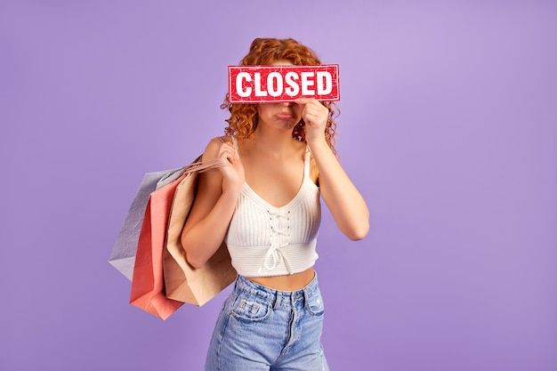 Linda chica pelirroja triste con rizos y bolsas de la compra con un cartel que dice cerrado aislado en púrpura