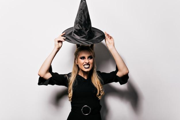 Linda chica de pelo largo divirtiéndose en el carnaval. impresionante dama posando con sombrero mágico en halloween.