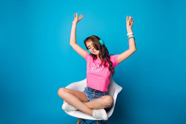 Linda chica con pelo largo y rizado escuchando música en silla sobre fondo azul. lleva pantalones cortos, camiseta rosa, zapatillas blancas. mantiene las piernas cruzadas en la silla y las manos por encima de la cabeza.