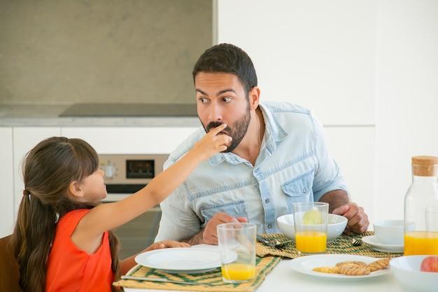 Linda chica de pelo negro dando una rebanada de comida a su padre para que la pruebe y muerda