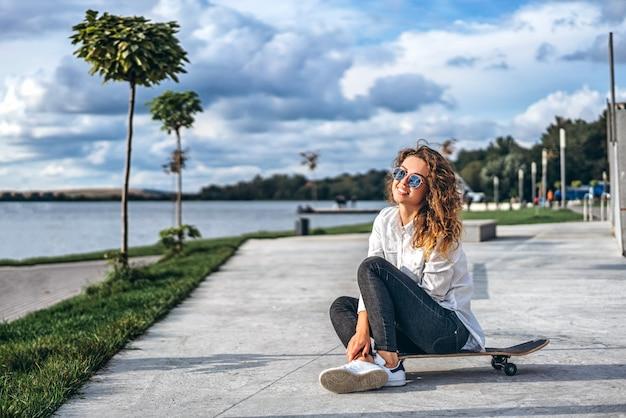 Linda chica con el pelo rizado con monopatín en el parque