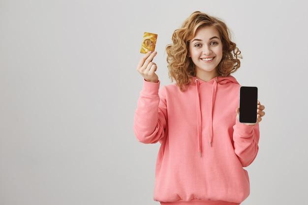 Linda chica de pelo rizado mostrando tarjeta de crédito dorada y pantalla de teléfono móvil