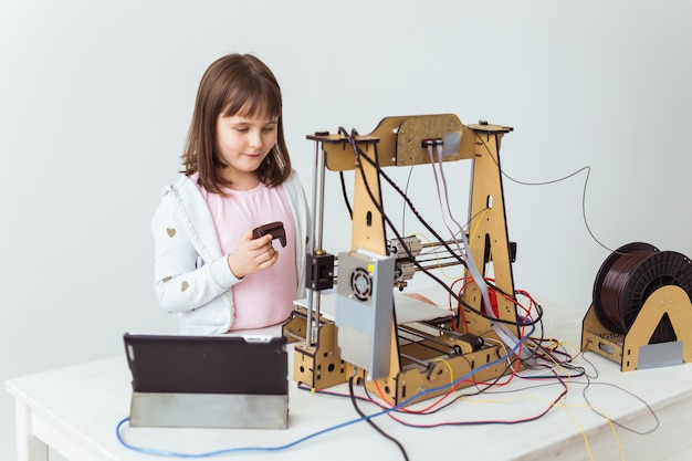 Linda chica con persianas impresas en 3d está mirando su impresora 3d mientras imprime su modelo 3d.