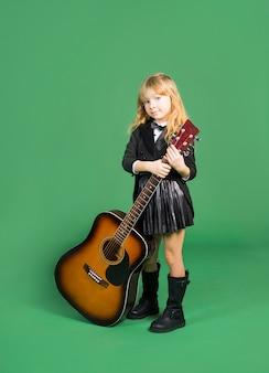 Linda chica de pie con guitarra acústica