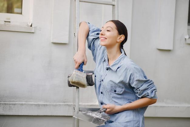Linda chica de pie junto a la pared con herramientas de reparación