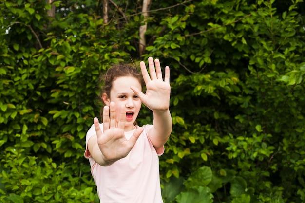 Linda chica de pie en el parque mostrando señal de stop