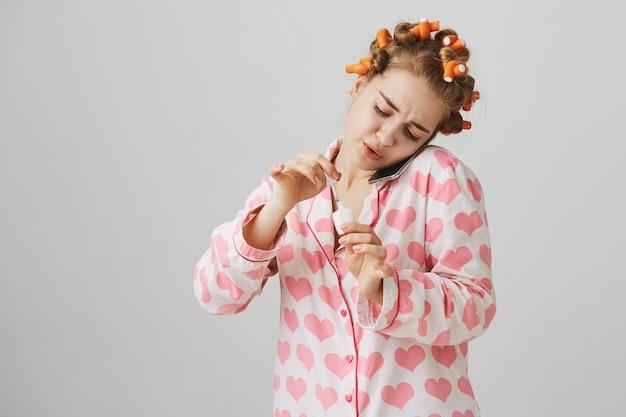 Linda chica en pijama y rizadores de pelo, hablando por teléfono mientras se aplica el esmalte de uñas