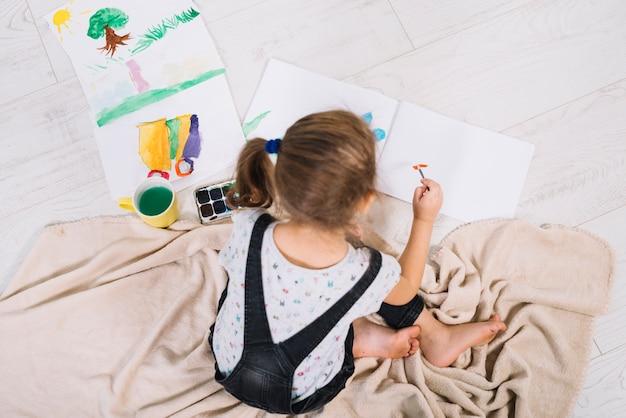 Linda chica pintando con acuarela en el piso