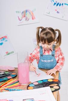 Linda chica pintando con acuarela sobre papel